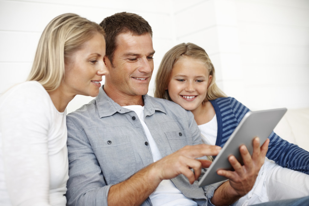 Portrait of handsome man with family using touchpad PC